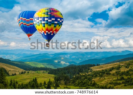 Stock Photo Colorful hot-air balloons flying over the mountains. Artistic picture. Beauty world