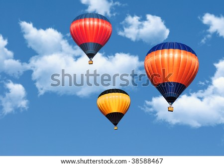 Colorful hot air balloons in the blue sky covered by clouds