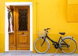 Colorful house on the island of Burano with a bike near the entrance