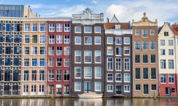 Colorful houses and boat at the Damrak in Amsterdam, Holland