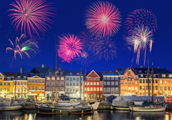 Colorful houses at Nyhavn Waterfront (Copenhagen, Denmark) with fireworks during New Year's celebration