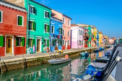 Colorful houses by a narrow canal in Burano, Italy