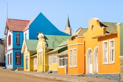 Colorful houses in Luderitz - Architecture concept with ancient german style town in south Namibia - Exclusive travel destination in african european settlement - Warm afternoon color tones