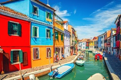 Colorful houses of Burano island. Multicolored buildings on fondamenta embankment of narrow water canal with fishing boats in sunny day, Venice Province, Veneto Region, Northern Italy. Burano postcard