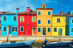 Colorful houses of Burano island. Multicolored buildings on fondamenta embankment of narrow water canal with fishing boats, Venice Province, Veneto Region, Northern Italy. Burano postcard