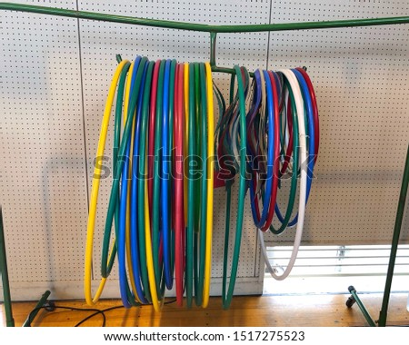 Colorful Hula Hoop Hoops on the metal hanger bar for students to play at a primary school #1517275523