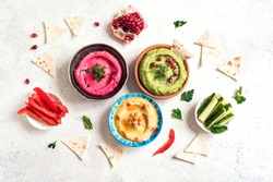 Colorful hummus bowls, healthy vegan dips. Traditional Middle eastern hummus, green hummus, beetroot hummus, spread. Assorted meze and dips with pita bread. Meze and snacks set, copy space.