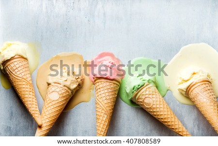 Photo of  Colorful ice cream cones of different flavors. Melting scoops. Top view, copy space, steel metal background