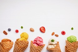 Colorful  ice cream with cones and various fruits raspberry ,blueberry ,strawberry ,almonds and peppermint leaves setup on white background . Summer and Sweet menu concept flat lay and copy space .