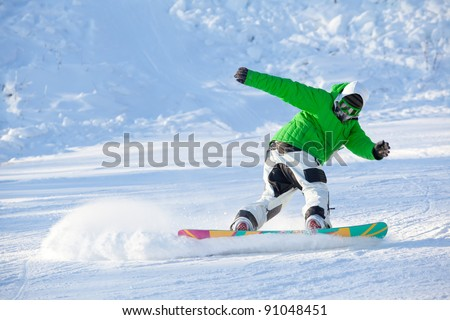 colorful image of young snowboarder in green jacket making powder turn trick on a ski slope