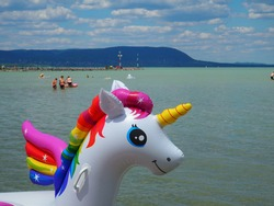 Colorful inflatable unicorn pony water toy in front of the beach strand of the lake Balaton in summer in Hungary