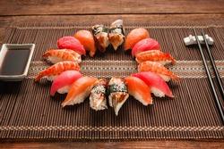 Colorful japanese sushi set, seafood. Great assortment of nigiri nigiri served like circle on brown straw mat, close up. National seafood, restaurant menu photo.