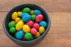 Colorful jelly beans candies in a bowl on wooden background. Sweet holiday treats for kids. Top view, copy space, selective focus