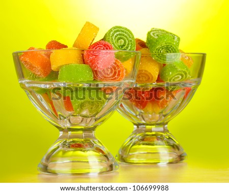 colorful jelly candies in  in glass bowls on green background