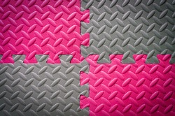 Colorful Jigsaw Foam flooring tiles or mat in grey and pink in metal floor look for anti slip and safety , vignette effect for background texture