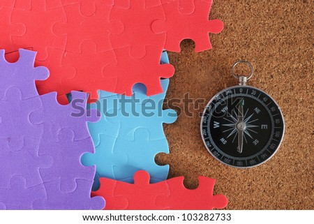 Colorful jigsaw puzzle with compass