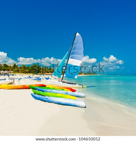 Colorful kayaks and sailing boats on a tropical beach in Cuba (Square format)
