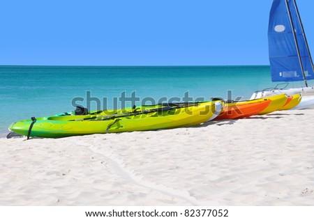Colorful kayaks on the ocean beach.