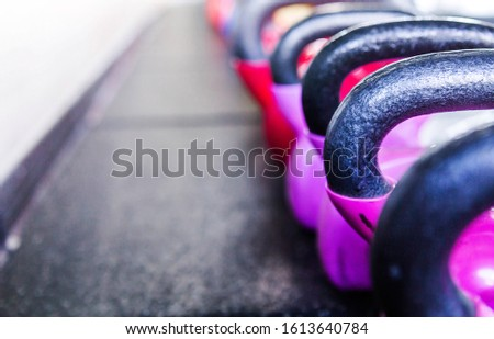 Colorful kettlebells in a gym. Red and violet