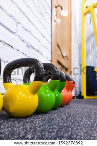 Colorful kettlebells in a row black fitness gym floor and white wall background with copy space