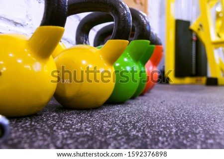 Colorful kettlebells in a row black gym floor background with copy space