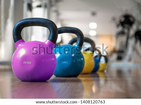 Colorful kettlebells in a row in a gym, purple, blue, yellow. - Image