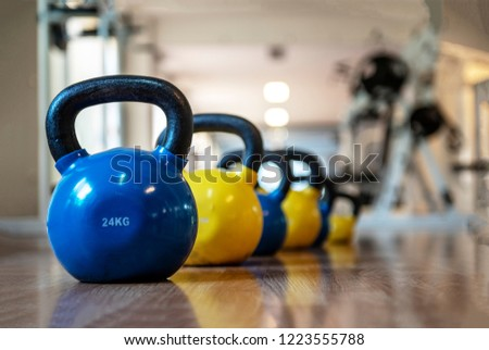 Colorful kettlebells in a row in a gym, yellow, blue,
