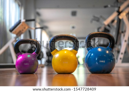 Colorful kettlebells in a row on floor in a gym, yellow color, blue color , pink color #1547728409