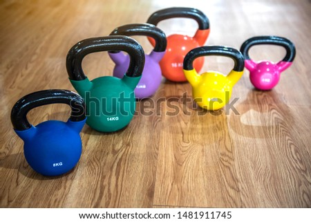 Colorful kettlebells in a row on wooden floor in a gym, blue, green,purple,orange,yellow and pink color