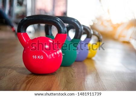 Colorful kettlebells in a row on wooden floor in a gym, red, green, purple and yellow color
