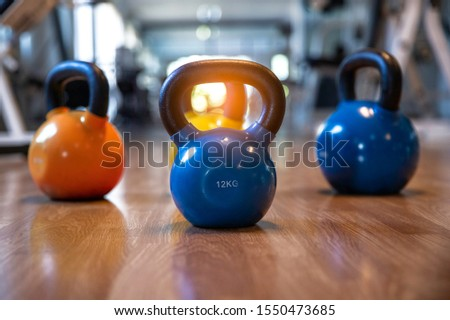 colorful kettlebells on wooden floor in gym, fitness center
