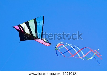 Colorful kite in flight against a blue sky.