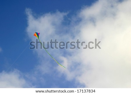 Colorful kite in flight against a blue sky with clouds