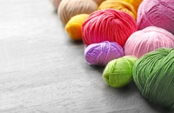 Colorful knitting yarn on wooden table