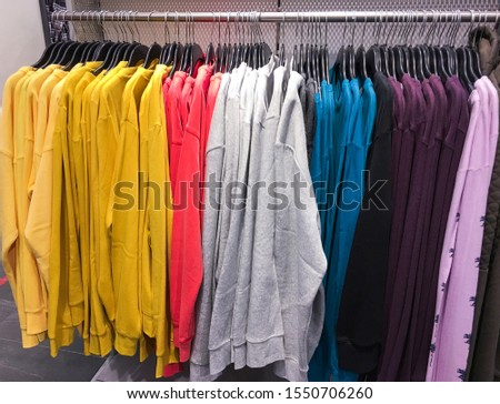 Colorful knitwear ,sweater ,white shirts, and different clothes are hanging on Clothes Hanger,