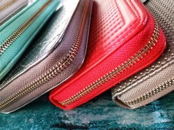Colorful lady purse stacked together at bag and leather shop.