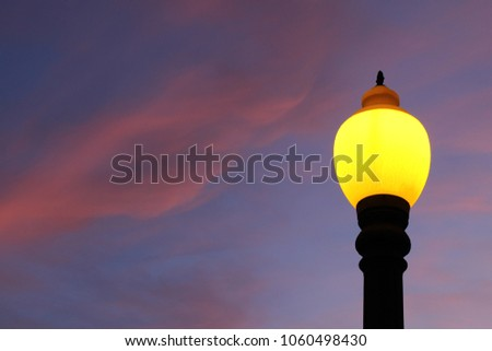 Colorful lamppost illuminating the afternoon. Blue sky and pink clouds in the background. #1060498430