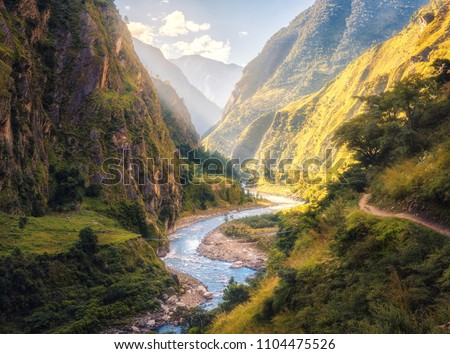 Colorful landscape with high Himalayan mountains, beautiful curving river, green forest, blue sky with clouds and yellow sunlight at sunset in summer in Nepal. Mountain valley. Travel in Himalayas #1104475526
