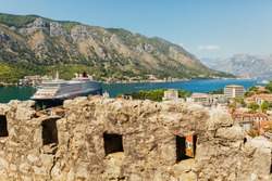 Colorful landscape with old walls in ancient citadel, sea, mountains, blue sky. Top view of Kotor bay with big cruise ship from medieval fortress. Historic landmark in Montenegro