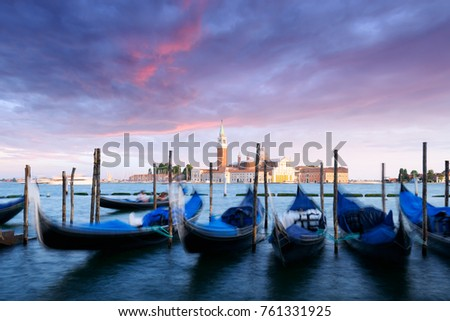Colorful landscape with orange sunset sky on piazza San Marco in Venice. Row of gondolas parked on city pier. Church of San Giorgio Maggiore on background, Italy, Europe