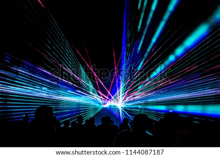 Colorful laser show nightlife club stage with party people crowd. Luxury entertainment with audience silhouettes in nightclub event, festival or New Year's Eve. Beams and rays shining colorful lights