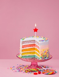 Colorful layered Birthday cake with sprinkles over a pink background.