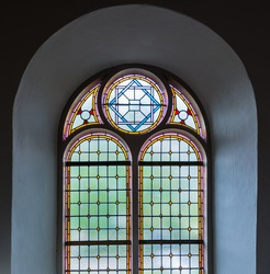 Colorful leaded glass window in a Dutch church from close.