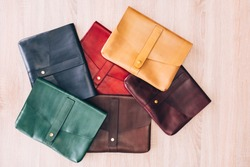 colorful leather bags laid out on the table. top view of the table with bags. Leather goods store. leather suitcase blue, red, yellow, green.