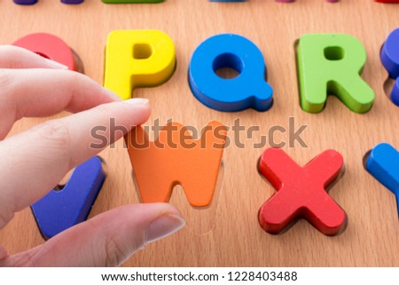 Colorful Letter of Alphabet W made of wood in hand #1228403488