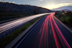 Colorful Light beams of moving vehicles on busy highway at dusk.