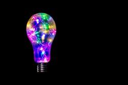 Colorful Light bulb lantern  isolated on black background. Lights shining, thinking concept. Brilliant idea inspiration celebrating concept.