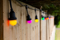 Colorful light bulbs lined up in a row, against a wooden garden fence. Bulbs are orange, pink, yellow and green. There are some green bushes and green grass in the background. It's a sunny Summer day.