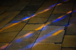 Colorful light spots on the tiled floor in the church. Sunlight filtered through the stained glass window.