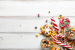 Colorful lollipops, candy canes and sweet candies mix on white wooden background